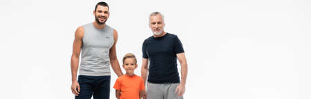 happy kid with grandpa and father in sportswear smiling at camera isolated on white, banner