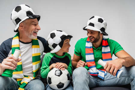 happy men in fan hats holding horns near boy with soccer ball isolated on gray