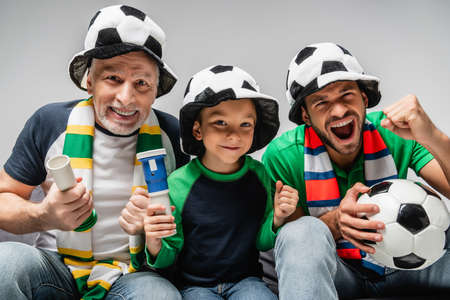 excited man screaming and showing win gesture near father and son in football fan hats isolated on gray
