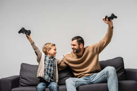 cheerful father and son showing win gesture with joysticks isolated on gray