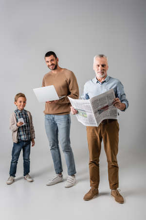 mature man holding newspaper near son and grandson with gadgets on gray