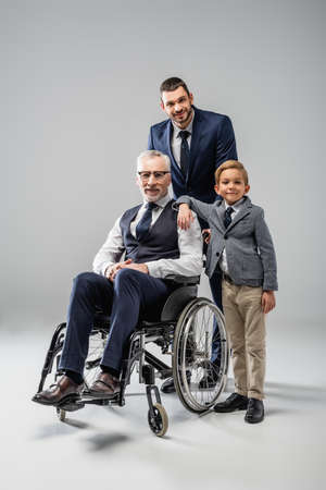 happy man in formal wear standing near son and father in wheelchair on gray