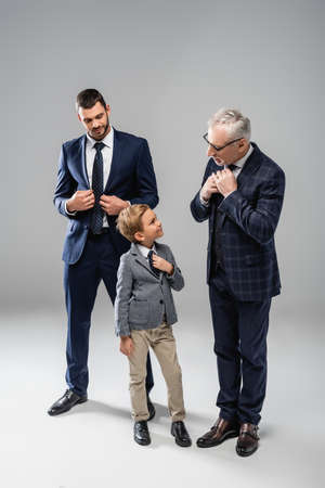 smiling businessman looking at grandfather and grandson touching ties on gray