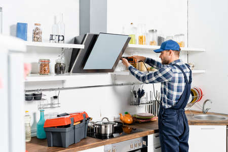young handyman using drill near extractor fan on blurred foreground in kitchen