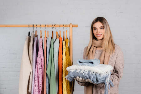 Smiling woman holding warm clothes near hanger rack with sweaters on white background