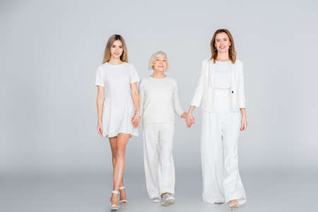 full length of three generation of happy women smiling while holding hands and walking on gray