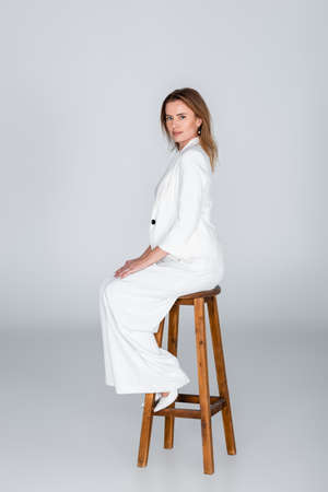 full length of woman in white outfit sitting on stool on gray