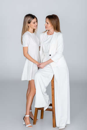 full length of young daughter and mother looking at each other on gray, generation of women