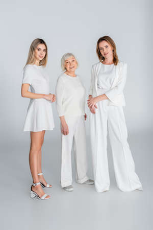 full length of three generation of happy women smiling while standing on gray