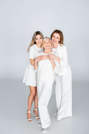 full length of three generation of happy women smiling while looking at camera on gray