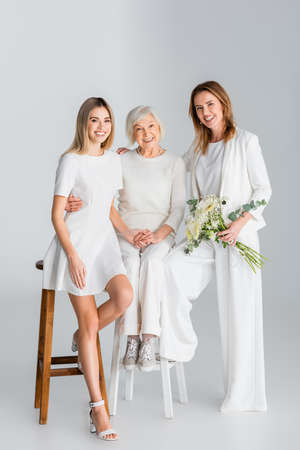 full length of happy woman holding flowers and smiling while sitting on chair with daughter and mother on gray