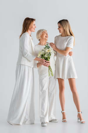 full length of happy senior woman holding flowers and smiling with daughter and granddaughter on gray