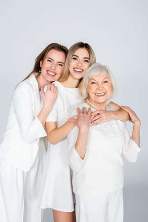 three generation of smiling women looking at camera and hugging isolated on gray