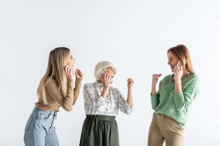 three generation of excited women talking on smartphones isolated on white