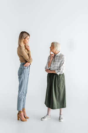 full length of thoughtful granddaughter and senior granny standing and looking at each other on white