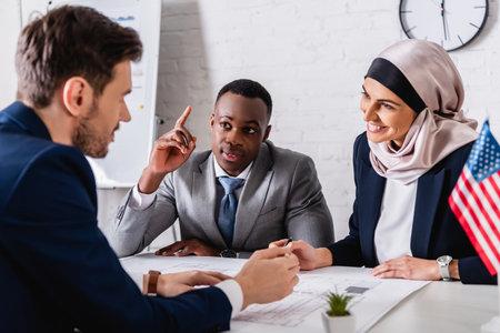 cheerful arabian businesswoman looking at interpreter near african american businessman showing idea gesture