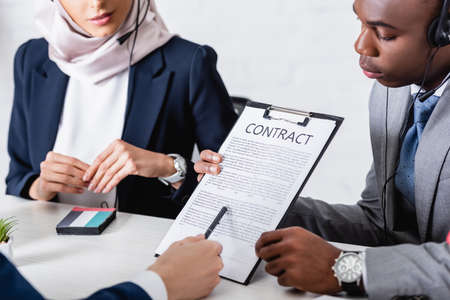 cropped view of interpreter pointing with pen at contract near african american and arabian business partners