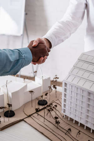 cropped view of interracial business partners shaking hands near models of building and alternative power station