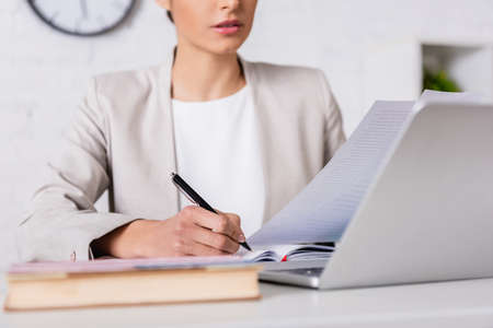 cropped view of translator writing in notebook while holding document near laptop, blurred foreground Stock fotó