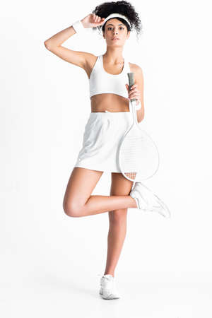full length of curly sportswoman adjusting cap while posing and holding tennis racket on white