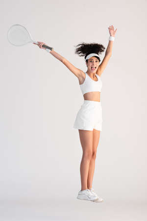 full length of excited woman in sportswear holding tennis racket and jumping on white