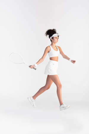 full length of curly young player in sportswear holding racket and playing tennis on white