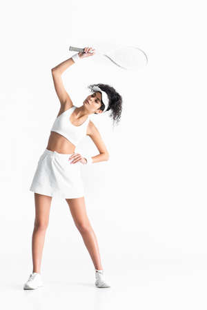 full length of curly sportswoman in cap holding tennis racket and exercising with hand on hip isolated on white