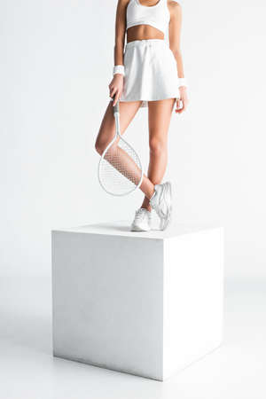 partial view of young sportswoman holding tennis racket and standing on cube on white