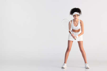 full length of curly player in sportswear holding racket and playing tennis on white