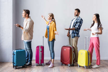 Angry multiethnic people with suitcases pointing with hands in hall of airport