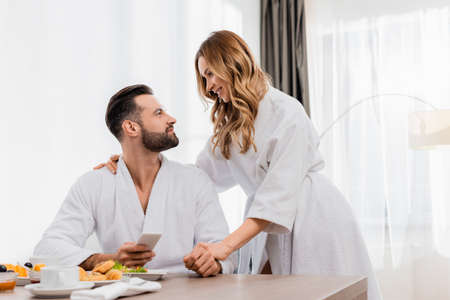 Smiling woman in bathrobe looking at boyfriend with smartphone near breakfast on blurred foreground in hotel