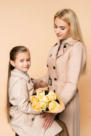 joyful kid holding roses near happy mother on 8 march isolated on beige
