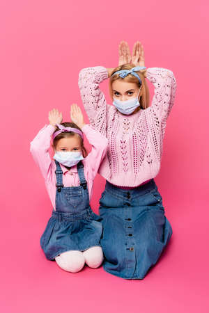 mother and daughter in medical masks making bunny ears with hands on pink