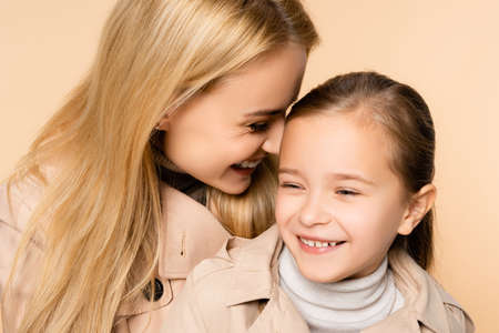 cheerful blonde mother and happy daughter laughing isolated on beige