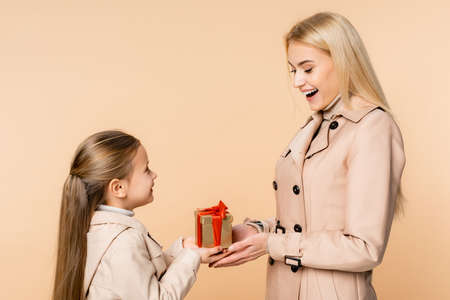 cheerful kid giving present to amazed mother on 8 march isolated on beige