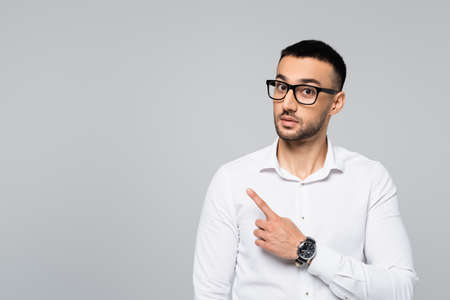 surprised hispanic businessman pointing aside with finger while looking at camera isolated on gray