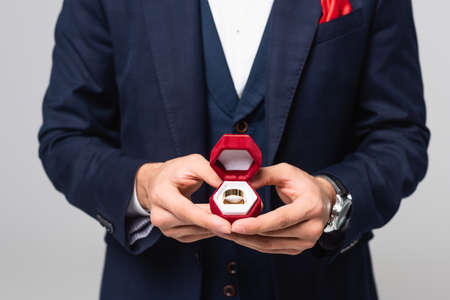 cropped view of elegant man holding jewelry box with wedding ring isolated on gray