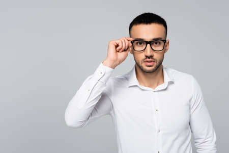 young hispanic manager in white shirt adjusting eyeglasses while looking at camera isolated on gray