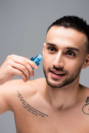 smiling, tattooed hispanic man holding vial of eau de cologne isolated on gray Stock Photo
