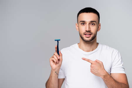 brunette hispanic man in white t-shirt pointing at safety razor isolated on gray