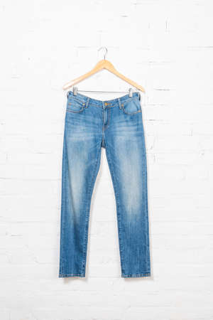 blue jeans on hanger near white brick wall