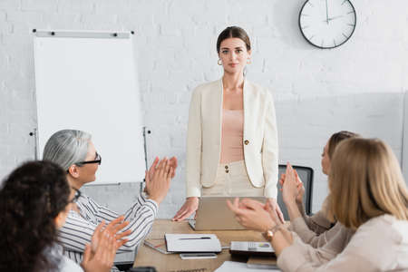 confident team leader looking at camera while multicultural audience applauding on blurred foreground Stock Photo