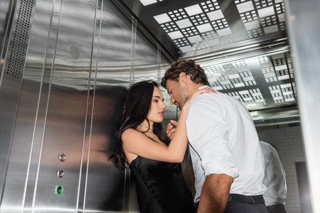 elegant man and woman in formal wear embracing in elevator