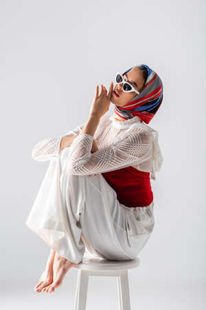 young trendy woman in headscarf and sunglasses sitting on stool while posing isolated on white Standard-Bild