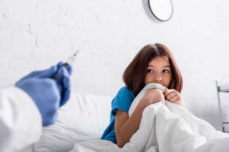 doctor holding syringe near scared girl sitting on bed under blanket