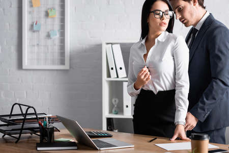young businessman near passionate secretary unbuttoning blouse near desk, blurred foreground