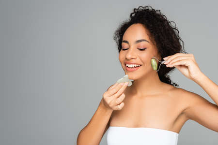 Young african american woman smiling while using jade roller and gua sha isolated on gray