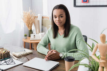 african american designer looking at camera while sitting at workplace at home