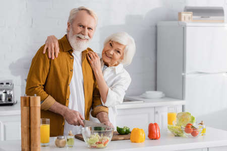 Smiling woman embracing senior husband cutting vegetables near orange juice and bowl in kitchen