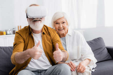 Senior man in virtual reality headset showing like near smiling wife at home Banque d'images